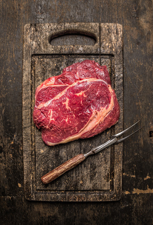 dark meat: Two raw beef ribeye steak with meat fork on dark rustic wooden gutting board, top view