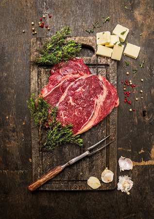 rare: Raw beef steak with thyme, butter and meat fork on dark rustic cutting board, top view Stock Photo