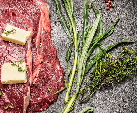dark meat: Raw meat with butter fresh tarragon and thyme on dark stone table top view close up Stock Photo