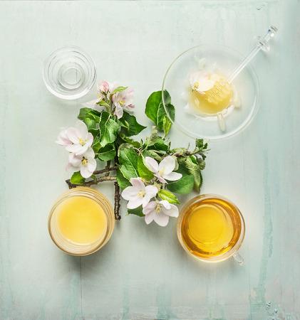 La cosecha de primavera miel en frasco de vidrio con el cazo flor fresca y una taza de té de la vista superior Foto de archivo - 40037553