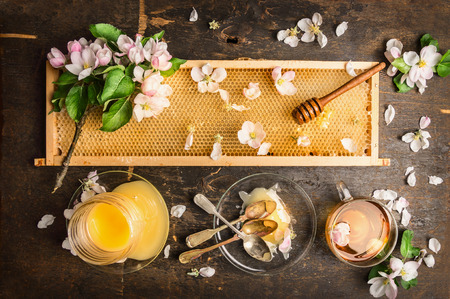 jars: Honeycomb with wooden dipper and fresh blossom with honey jar and plate with vintage spoons on dark rustic background top view