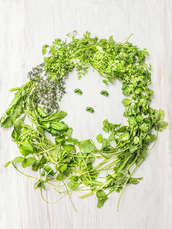 withe: Fresh green herbs and salad woman face on withe wooden background top view healthy food concept Stock Photo