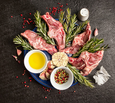 lamb cutlet with oil Herbs and spices on dark background top view photo