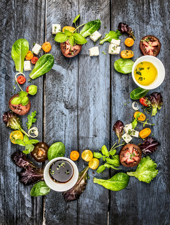Colorful salad ingredients with tomatoes and feta cheese on rustic blue wooden background round frame top view