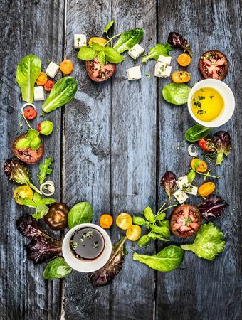 ensalada de verduras: Ingredientes de la ensalada de colores con tomate y queso feta sobre fondo azul de madera vista superior marco redondo r�stico