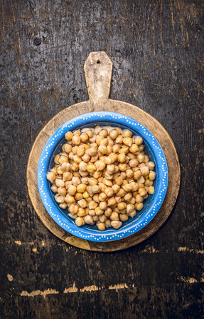 Chick peas hummus in blue bowl with water on rustic wooden background Top View