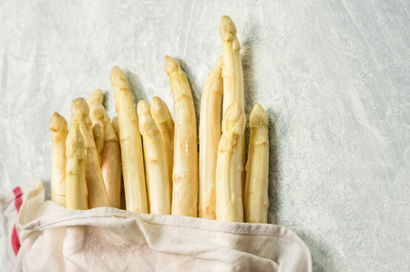 Fresh white asparagus with wet kitchen towel on gray wooden background Top View