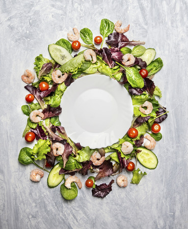 Shrimp salad with lettuce and tomatoes around white empty plate on light gray wooden background Top View copyspace