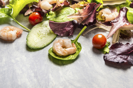 Colorful fresh salad with cucumber and shrimps close up place for text photo