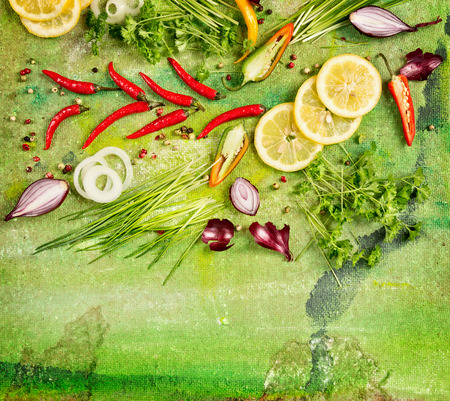 Fresh herbs and spices Ingredients for cooking on green background top view frame photo