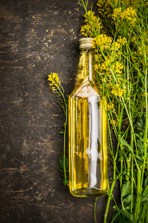 Bottle of Rape oil on rustic wooden background Top View