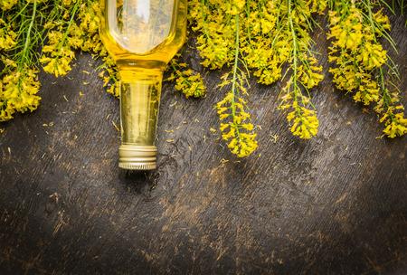 暗い背景の素朴な木の上に菜種油と菜の花の花がテキストの場所を表示します。 写真素材