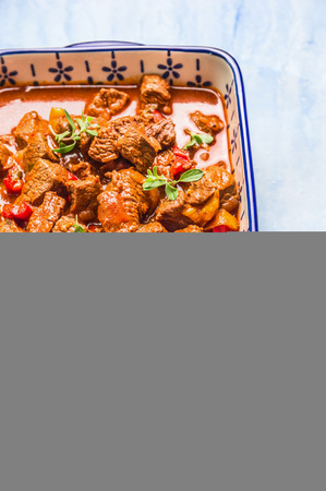 beef meat: eef goulash in casserole dish on light wooden background