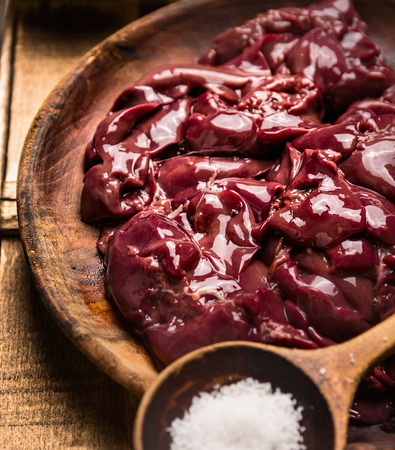 entrails: Raw chicken liver in wooden dish with spoon of salt Stock Photo