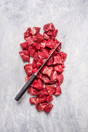 stewing: chopped meat with knife on light wooden background Top View