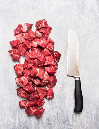 Raw beef goulash meat diced for stew with meat knife on light gray wooden background Top View