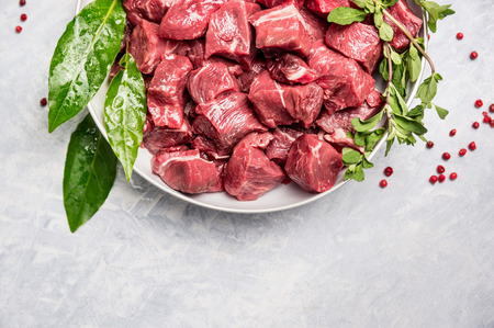 Chopped raw beef meat in white bowl with fresh herbs on light wooden background Top View