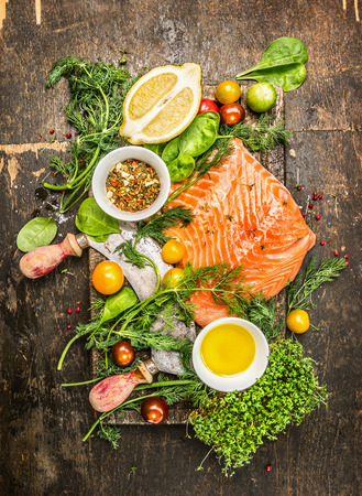 food fish: Fresh salmon fillet with fresh healthy herbsvegetables oil and spices on rustic wooden background Top View