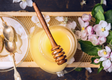 Top view of honey jar with wooden spoon and dipper spring blossom on Honeycomb and rustic wooden background Stock Photo
