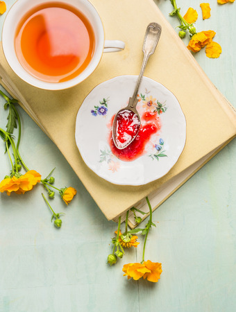 Breakfast scene: cup of tea plate with red jam and vintage spoon on a book and yellow garden flowers still life