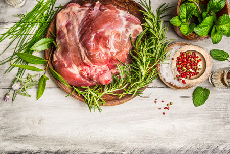 Raw leg of lamb with fresh herb on white rustic wooden background top view place for text frame