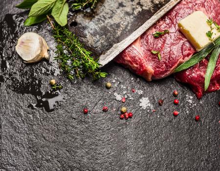 carne cruda: Filete de carne cruda con mantequilla condimentos frescos y hoja de cuchillo de edad en el fondo de piedra oscura vista superior horizontal