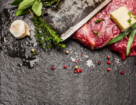 red  stone: Raw meat steak with butter fresh seasonings and blade of old knife on dark stone background top view horizontal