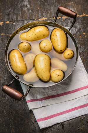 Fresh new potatoes in pan with water on old rustic wooden background Top View