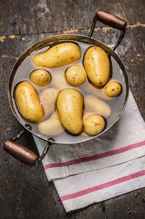 papas: Nuevas patatas frescas en la cacerola con agua en viejo fondo de madera rústica Vista Superior