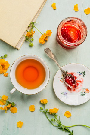 over: Cup of tea with jam jar book and yellow flowers top view
