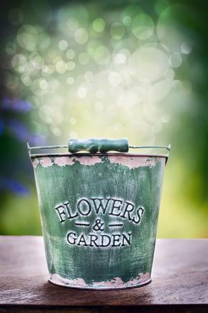 blue toned: Empty green old bucket on wooden table over green park or garden background with light bokeh