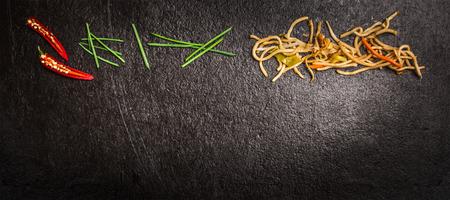 緑のチャイブとコンセプトの料理のウェブサイトの暗いスレート背景トップ ビュー バナーを赤唐辛子でアジア麺