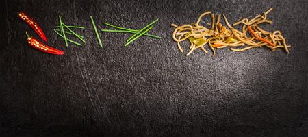 Asian noodles with green chives and red chili on dark slate background top view banner for website with cooking concept Imagens