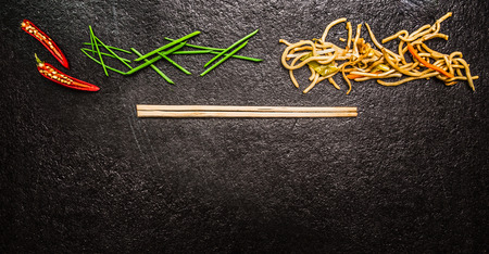 noodles: Asian noodles with chopstick red chili chopped chives on black slate background top view banner for website