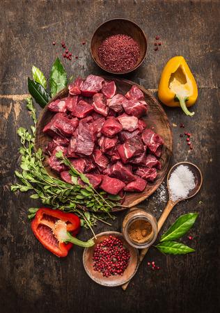 cebolla blanca: Carne cruda sin procesar rebanadas en cubos con hierbas frescas, verduras y especias sobre fondo de madera rústica, ingredientes para la receta de estofado de carne, vista desde arriba