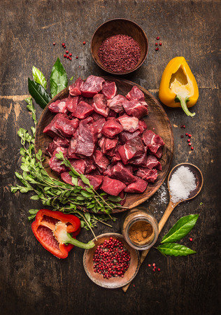 Raw  uncooked meat sliced in cubes with fresh herbs, vegetables and spices on rustic wooden background, ingredients for beef stew recipe, top view