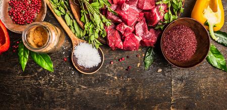 Ingrediënten voor goulash of stamppot koken: rauw vlees, kruiden, specerijen, groenten en lepel zout op rustieke houten achtergrond, bovenaanzicht. Banner voor de website.