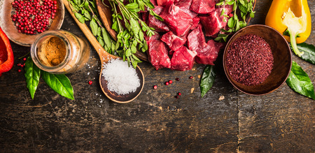 goulash: Ingredients for goulash or stew cooking: raw meat, herbs,spices,vegetables and spoon of salt on rustic wooden background, top view. Banner for website.