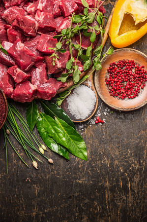 Chopped raw meat with vegetables, herb and spices for goulash on  rustic wooden background, top view, place for text