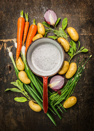 fresh pot: Fresh organic vegetables and herbs around old empty cooking pot on rustic wooden background, top view composing, copy space