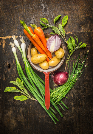 eating in the garden: Garden vegetables ingredients in old cooking pot on rustic wooden background, top view Stock Photo
