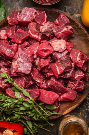 Raw  uncooked meat sliced in cubes on wooden rustic background, top view, close up 스톡 콘텐츠