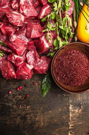 snijden van rauw vlees met kruiden en verse kruiden, ingrediënten voor goulash koken op rustieke houten achtergrond, bovenaanzicht, plaats voor tekst