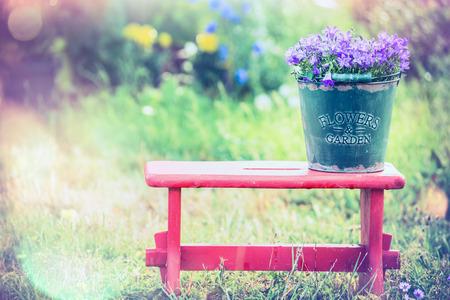casa de campo: cubo de la vendimia con las flores del jardín en taburete rojo sobre fondo de la naturaleza del verano