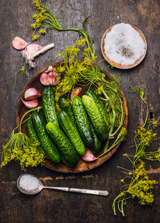 pickling: Cucumbers, herbs and spices for pickling on rustic wooden background, top view