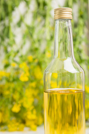 oil rape: Glass bottle of rapeseed oil on rape blossoms background, close up