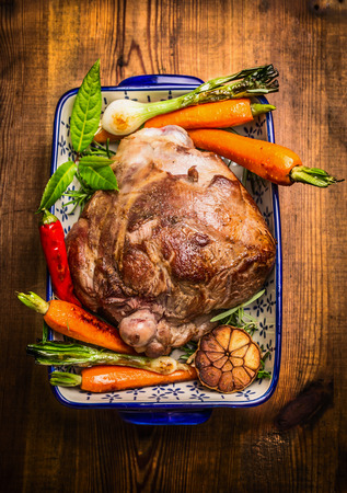 Roast lamb leg with vegetables and fresh herbs in blue casserole bowl on rustic wooden background, top view