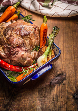 Roasted leg of lamb with herbs and vegetables on wooden background
