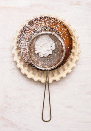 sifter: Old powdered sugar sifter spoon on white wooden background, top view Stock Photo