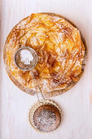 filo pastry: Filo pastry pie and powdered sugar Sifter Spoon on white wooden background, top view Stock Photo